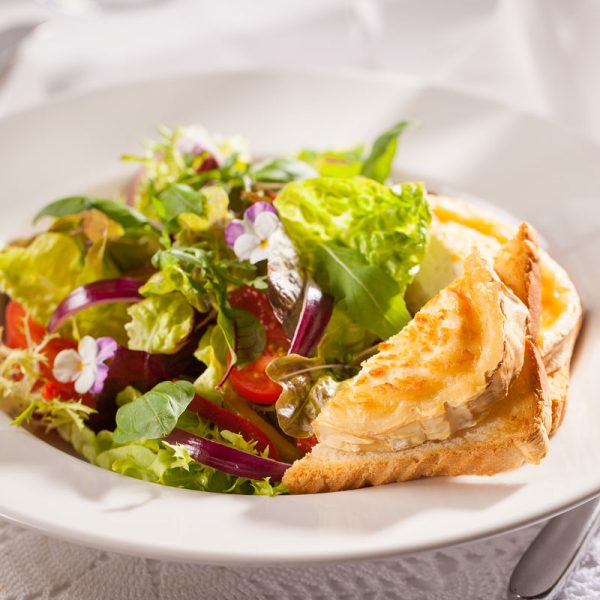 Green salads with roasted peppers and goat cheese